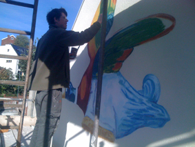 Artist working on the mural